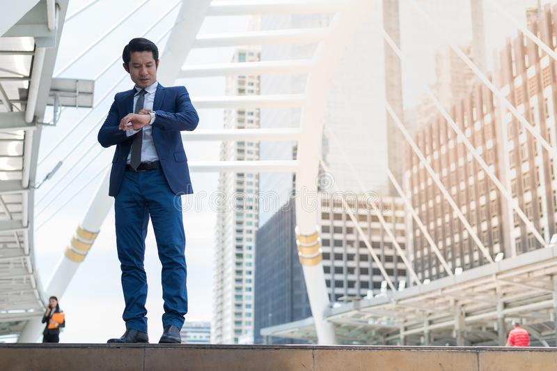Η ασιατική στάση επιχειρηματιών στην πόλη και εξετάζει το ρολόι στα χέρια του Πηγαίνει να εργαστεί αργά στοκ εικόνες με δικαίωμα ελεύθερης χρήσης