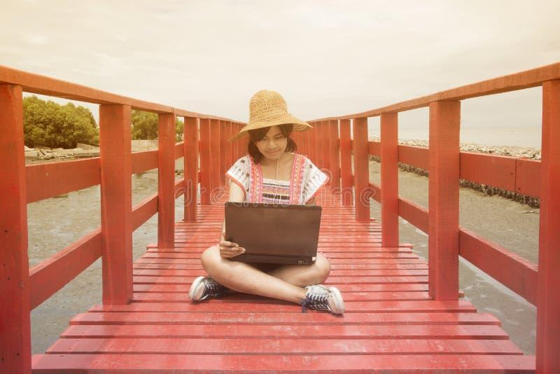 Η ασιατική συνεδρίαση γυναικών λειτουργεί ένα lap-top στην κόκκινη ξύλινη γέφυρα στοκ εικόνες
