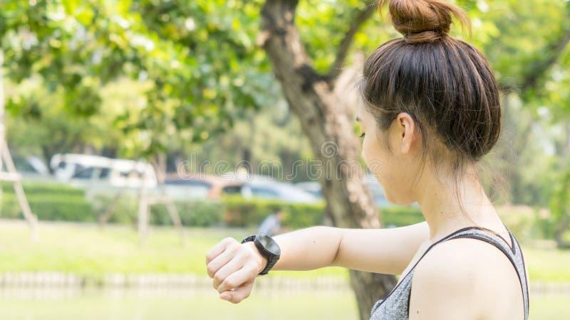 Η ασιατική χαριτωμένη υγιής κατάλληλη και σταθερή λεπτή κυρία εφήβων εξετάζει τον έξυπνο στοκ φωτογραφία με δικαίωμα ελεύθερης χρήσης