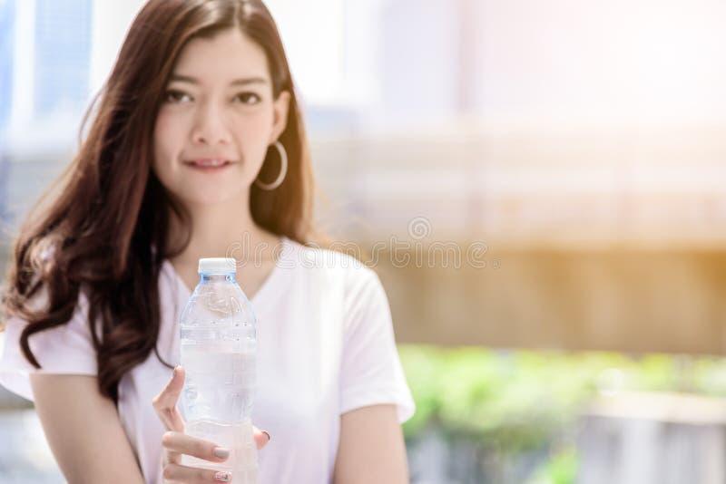 Η ασιατική όμορφη γυναίκα έχει την κατανάλωση νερού με το υπόβαθρο πόλεων στοκ φωτογραφία