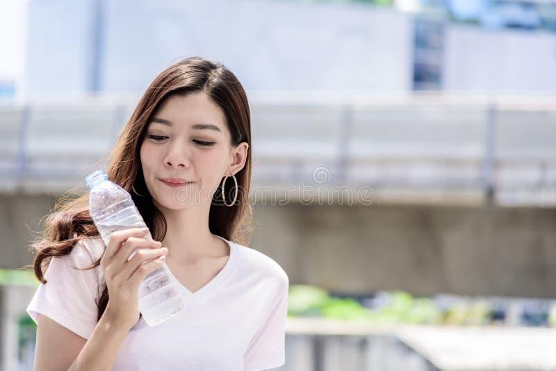 Η ασιατική όμορφη γυναίκα έχει την κατανάλωση νερού με το υπόβαθρο πόλεων στοκ φωτογραφίες