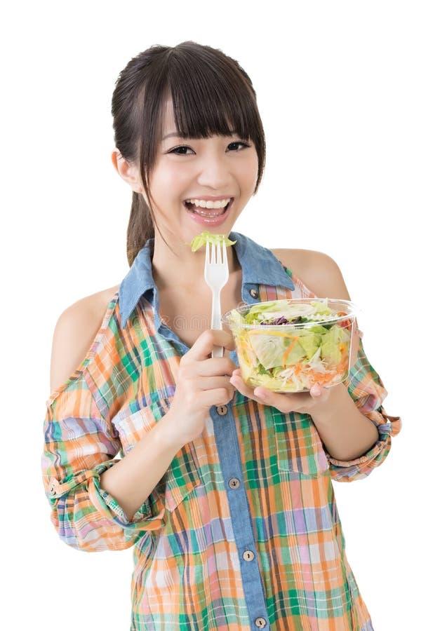 Η ασιατική όμορφη γυναίκα τρώει τη σαλάτα στοκ εικόνες