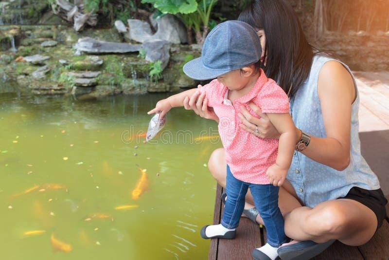 Η ασιατική όμορφη μητέρα είναι παίρνει την προσοχή τα χαριτωμένα ταΐζοντας ψάρια μωρών σας στοκ εικόνες