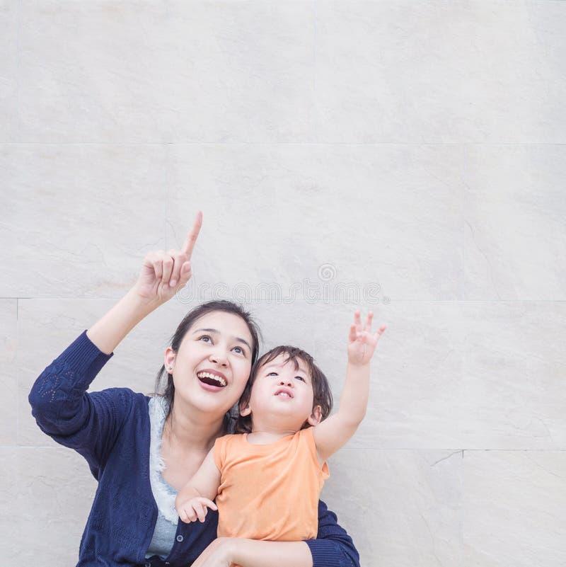 Η ασιατικοί μητέρα και ο γιος κινηματογραφήσεων σε πρώτο πλάνο δείχνουν το διάστημα αντιγράφων της εικόνας στο μαρμάρινο κατασκευ στοκ φωτογραφία