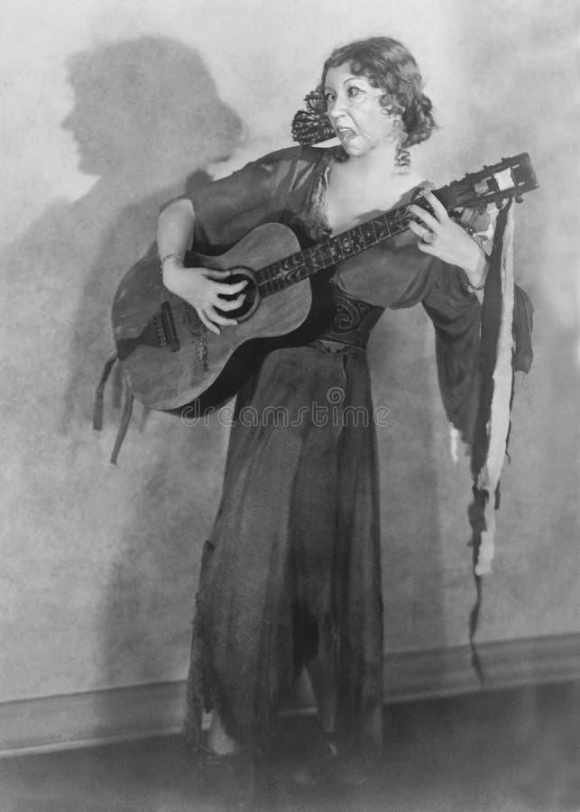 Η αστεία εκλεκτής ποιότητας κιθάρα, τραγουδιστής, γυναίκα, τραγουδά στοκ φωτογραφίες
