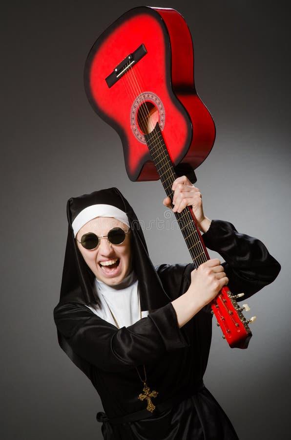 Η αστεία καλόγρια με το κόκκινο παιχνίδι κιθάρων στοκ φωτογραφία με δικαίωμα ελεύθερης χρήσης