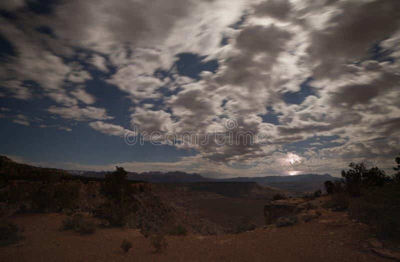Η αστραπή χτυπά ανατολικά το εθνικό πάρκο Zion ενώ το φεγγάρι και τα αστέρια ανάβουν τα σπασμένα σύννεφα επάνω από τα mesas της ν στοκ εικόνα