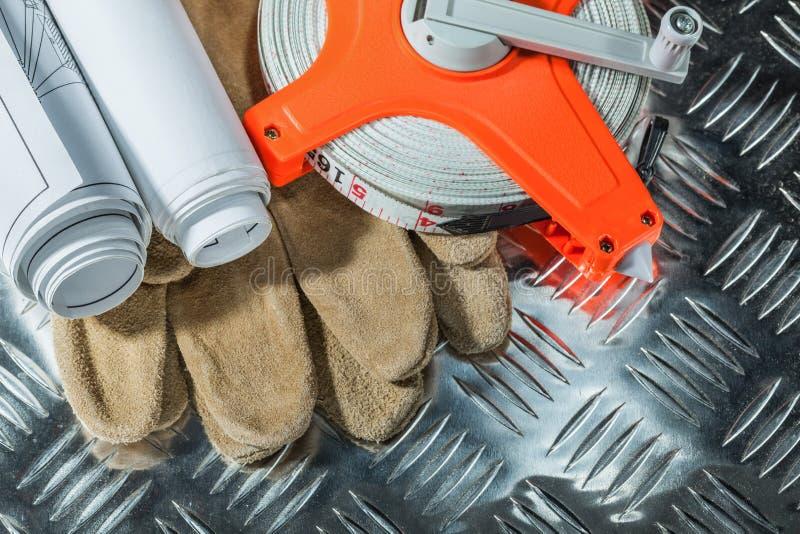 Η ασφάλεια δέρματος φορά γάντια στα κατασκευαστικά σχέδια μέτρου ταινιών στο corr στοκ εικόνα με δικαίωμα ελεύθερης χρήσης