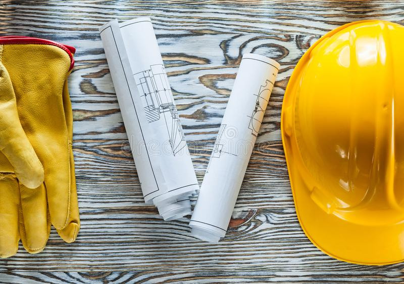 Η ασφάλεια φορά γάντια στα σκληρά σχεδιαγράμματα καπέλων στον ξύλινο πίνακα στοκ εικόνες