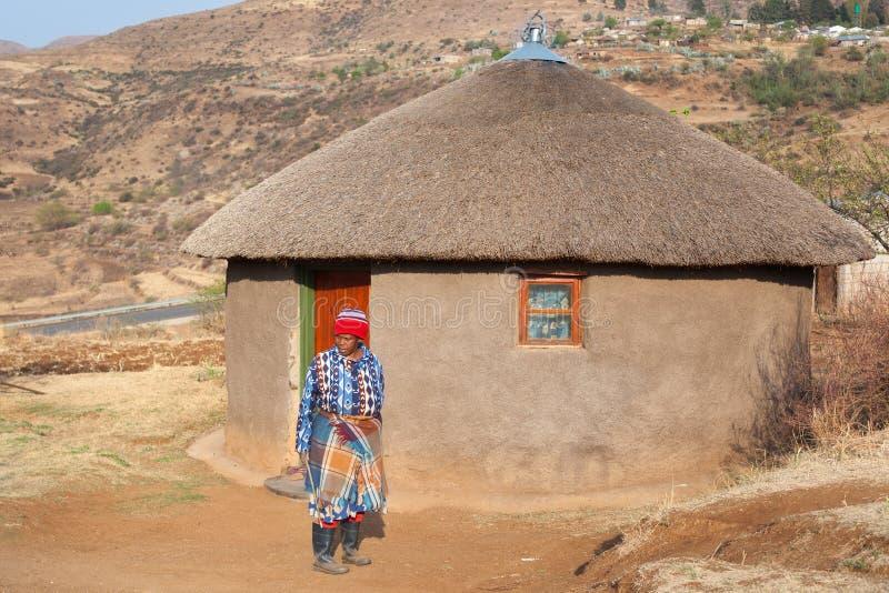 Η αφρικανική γυναίκα στο παραδοσιακό γενικό φόρεμα στο αυθεντικό χωριό, ηλικιωμένη γυναίκα basotho κοντά στον άργιλό της γύρω από στοκ εικόνα