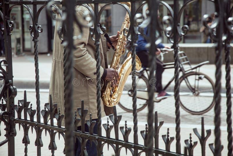 Η αφρικανική παίζοντας τζαζ μουσικών οδών στο saxophone ρίχνει το δικτυωτό πλέγμα με τη σκιαγραφία ποδηλάτων, ζωή πόλεων στο Άμστ στοκ εικόνα με δικαίωμα ελεύθερης χρήσης