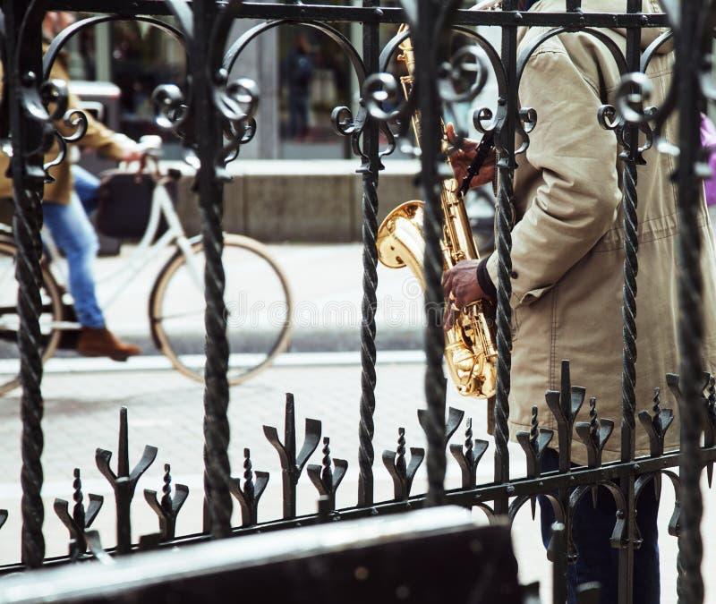 Η αφρικανική παίζοντας τζαζ μουσικών οδών στο saxophone ρίχνει το δικτυωτό πλέγμα στοκ εικόνες