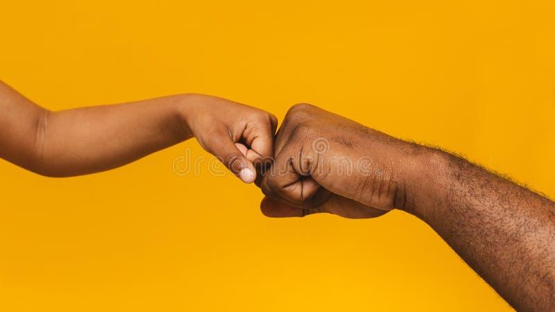 Η αφρικανική πρόσκρουση πυγμών ατόμων και μικρών κοριτσιών, κλείνει επάνω στοκ φωτογραφίες