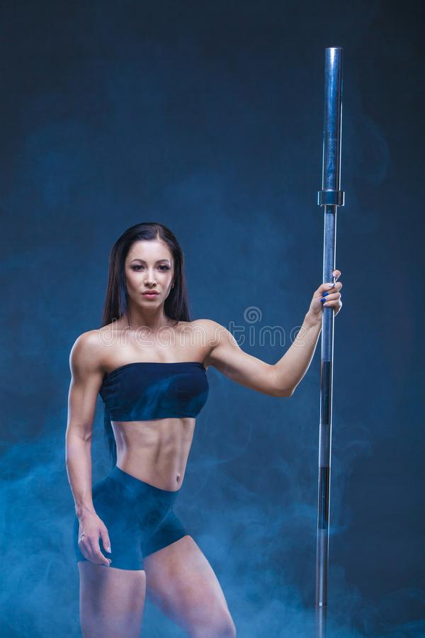 Η βάναυση αθλητική προκλητική γυναίκα κρατά ένα barbell Η έννοια του αθλητισμού άσκησης, που διαφημίζει μια γυμναστική Στο Μαύρο στοκ φωτογραφίες με δικαίωμα ελεύθερης χρήσης