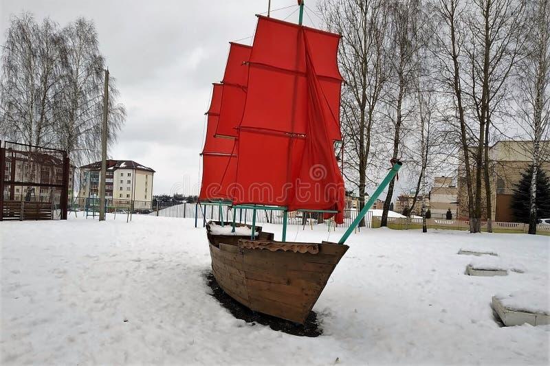Η βάρκα με τα φωτεινά κόκκινα πανιά, εγκατάσταση, σχέδιο, ένα ναυπηγείο σχολικών δικαστηρίων, χειμώνας, χιόνι, στοκ εικόνα