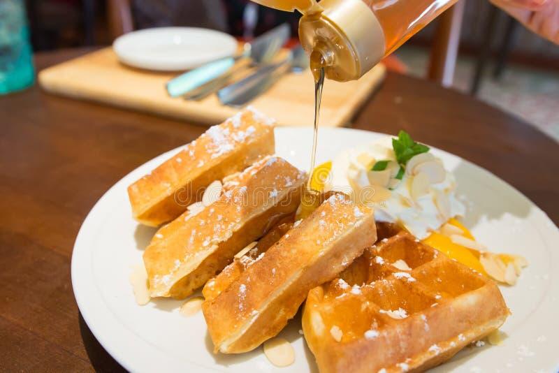 Η βάφλα ροδάκινων με κτυπά την κρέμα και το χύνοντας μέλι στοκ εικόνες