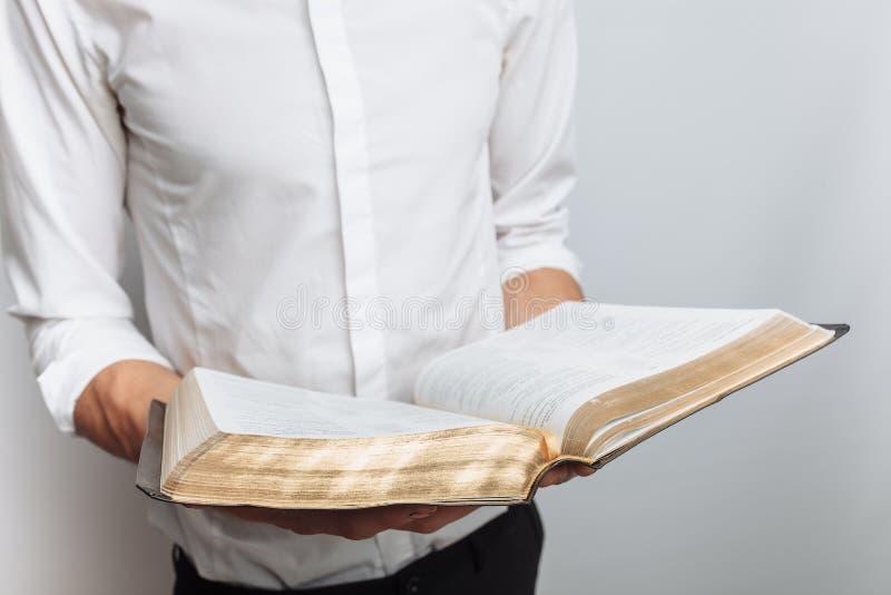 Η Βίβλος ανάγνωσης ατόμων, άσπρο υπόβαθρο, κρατά τη διαθέσιμη κινηματογράφηση σε πρώτο πλάνο χεριών στοκ εικόνες με δικαίωμα ελεύθερης χρήσης