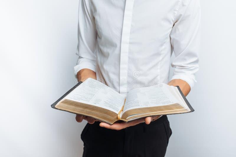 Η Βίβλος ανάγνωσης ατόμων, άσπρο υπόβαθρο, κρατά τη διαθέσιμη κινηματογράφηση σε πρώτο πλάνο χεριών στοκ φωτογραφίες με δικαίωμα ελεύθερης χρήσης