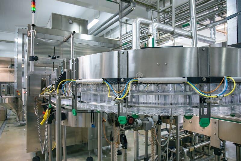 Η βιομηχανική παραγωγή και η ζώνη μεταφορέων ot ευθυγραμμίζουν τη μηχανή των πλαστικών μπουκαλιών κατοικίδιων ζώων στις εγκαταστά στοκ εικόνες