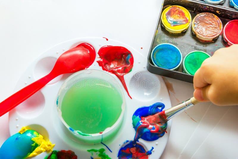 Η βούρτσα εκμετάλλευσης χεριών του παιδιού βύθισε στο χρώμα στο υπόβαθρο της Λευκής Βίβλου με το διάφορο tempera watercolor γκουα στοκ φωτογραφία
