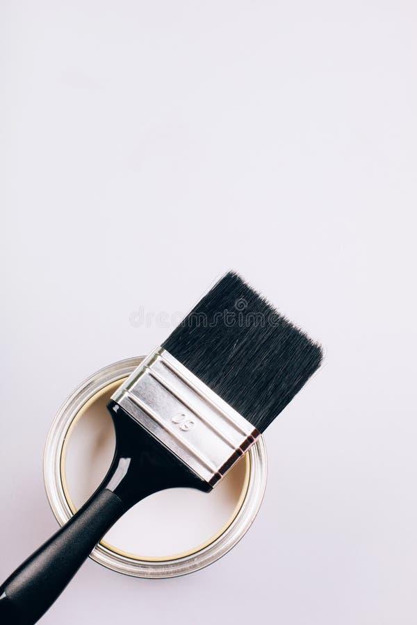 Η βούρτσα με τη μαύρη λαβή σε ανοικτό μπορεί άσπρου να χρωματίσει στο γκρίζο υπόβαθρο στοκ φωτογραφία