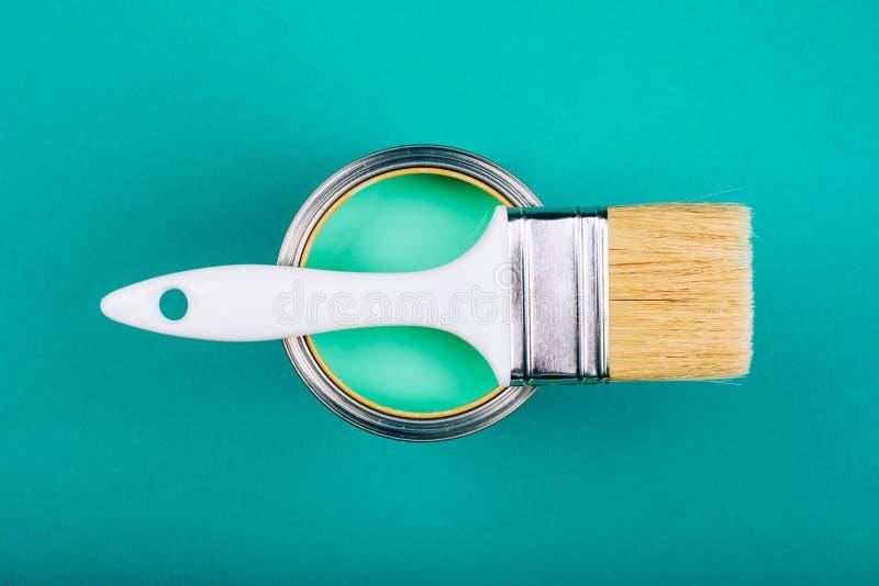 Η βούρτσα σε ανοικτό μπορεί με τυρκουάζ να χρωματίσει του χρώματος στο μπλε υπόβαθρο στοκ φωτογραφίες