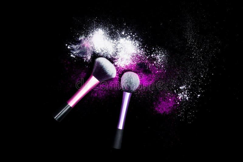 Η βούρτσα σύνθεσης με την άσπρη σκόνη που ανατρέπεται ακτινοβολεί σκόνη στο μαύρο υπόβαθρο Βούρτσα Makeup στο νέο κόμμα έτους ` s στοκ φωτογραφία με δικαίωμα ελεύθερης χρήσης