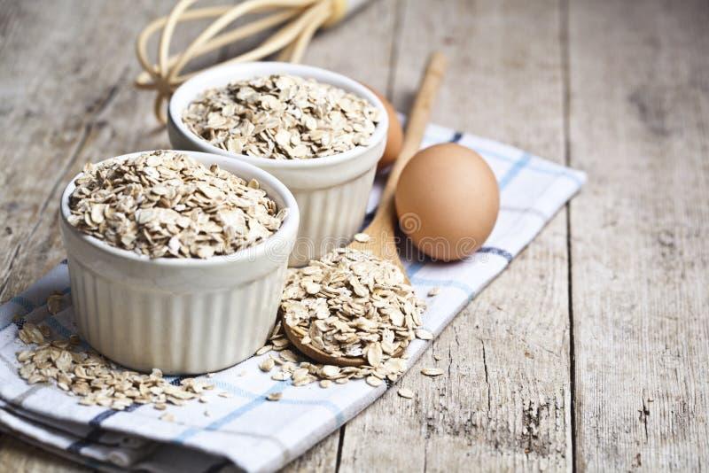 Η βρώμη ξεφλουδίζει στα κεραμικά κύπελλα και το ξύλινο κουτάλι και τα φρέσκα αυγά κοτόπουλου στο αγροτικό ξύλινο επιτραπέζιο υπόβ στοκ φωτογραφία