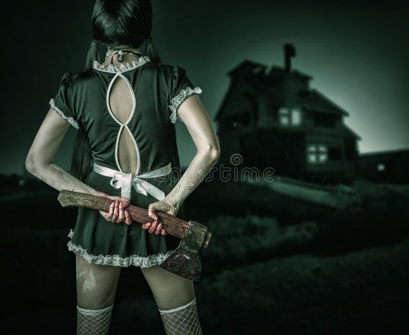 Η βρώμικη γυναίκα στέκεται την πίσω εκμετάλλευση ένα αιματηρό τσεκούρι στοκ εικόνες με δικαίωμα ελεύθερης χρήσης