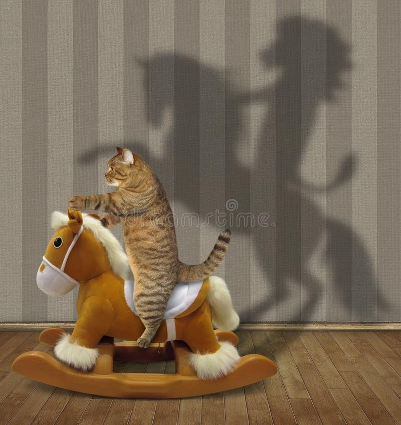 Η γάτα οδηγά ένα άλογο λικνίσματος παιχνιδιών στοκ εικόνες