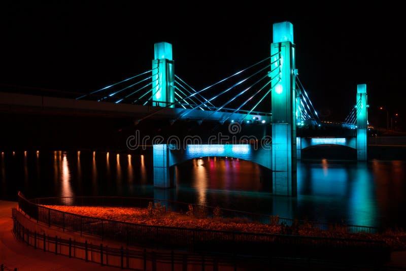 Η γέφυρα πέρα από τον ποταμό Brazos που φωτίστηκε από τις οδηγήσεις σε Waco, Τέξας/φως χρωμάτισε τη γέφυρα στοκ φωτογραφία