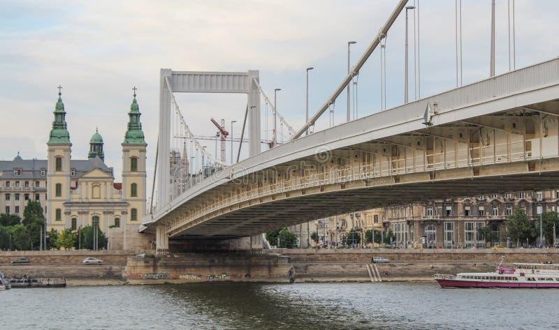 Η γέφυρα της Βουδαπέστης Elisabeth στον ποταμό Δούναβη με την εκκλησία μητέρων καρδιών της πόλης στο υπόβαθρο στοκ εικόνες με δικαίωμα ελεύθερης χρήσης