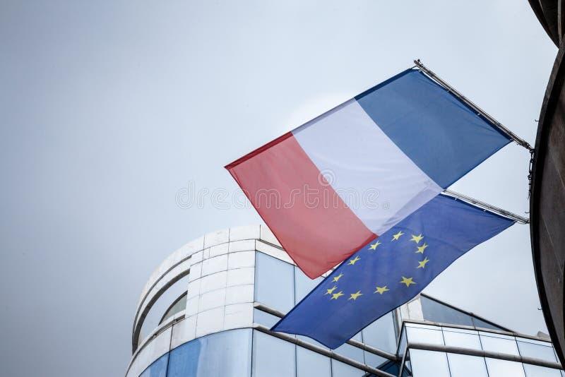 Η γαλλική σημαία και η Ευρωπαϊκή Ένωση σημαιοστολίζουν τη στάση μπροστά από ένα επιχειρησιακό κτήριο, να παραμερίσουν στοκ εικόνα