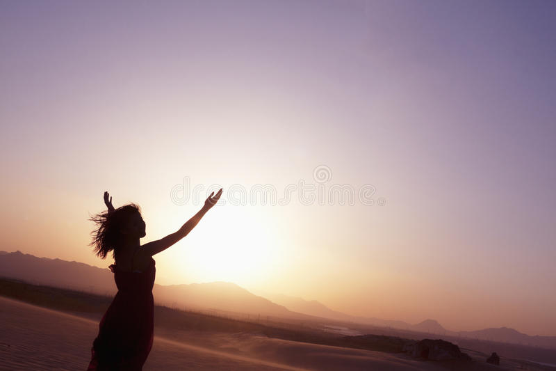 Η γαλήνια νέα γυναίκα με τα όπλα να κάνει τη γιόγκα στην έρημο στην Κίνα, σκιαγραφία στοκ εικόνες