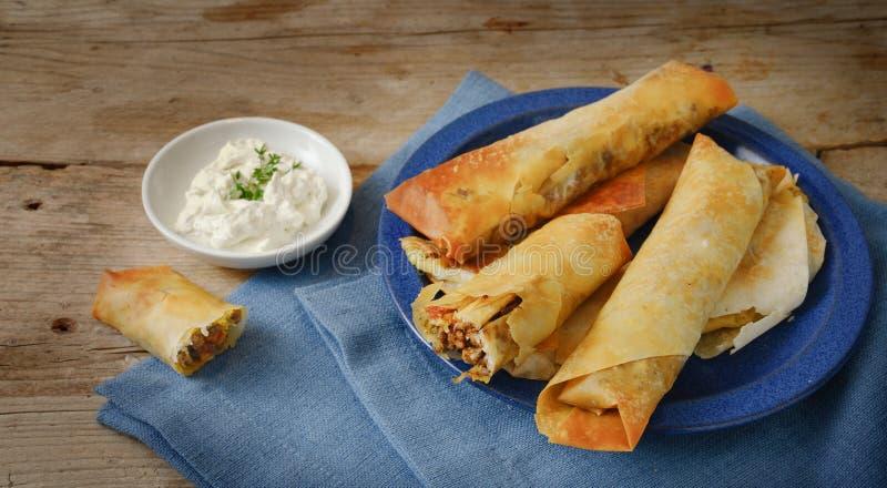 Η γεμισμένη ζύμη filo ή yufka κυλούν και το τυρί στάρπης, ζύμη με μια πικάντικη πλήρωση κρέατος, μπλε πετσέτα σε έναν αγροτικό ξύ στοκ εικόνες με δικαίωμα ελεύθερης χρήσης