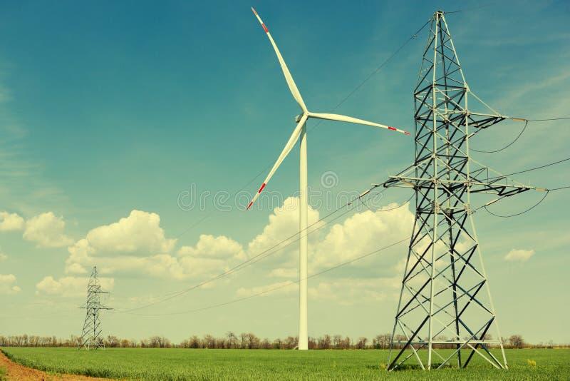 Η γεννήτρια τουρμπίνας αέρα και οι υψηλής τάσεως πόλοι γραμμών στέκονται σε έναν τομέα του πράσινου νέου σίτου, η έννοια στοκ φωτογραφία με δικαίωμα ελεύθερης χρήσης