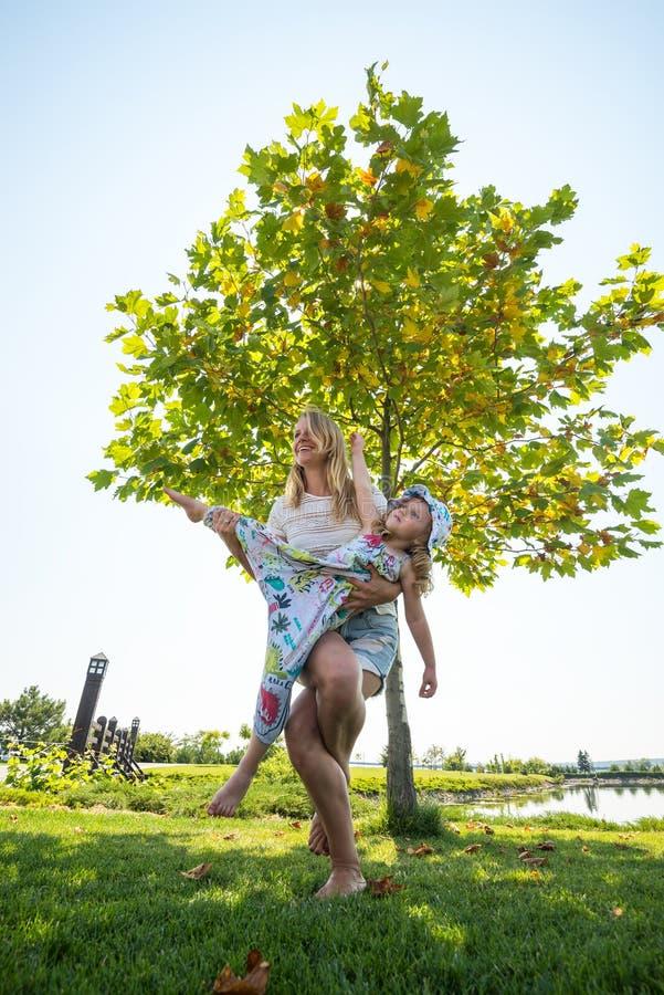 Η γελώντας νέα μητέρα συμμετέχει στη γιόγκα με την λίγο daughte στοκ φωτογραφίες