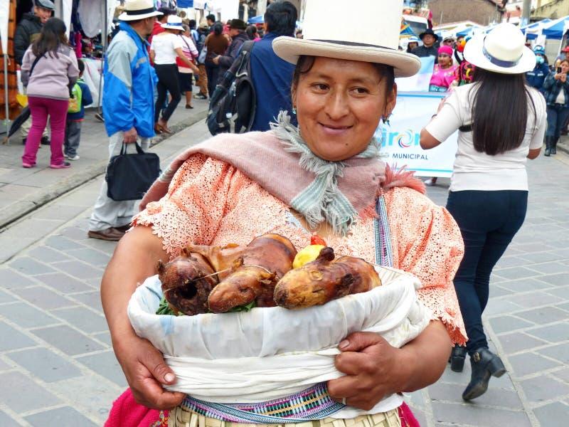 Η γηγενής γυναίκα κρατά το καλάθι με τα ψημένα στη σχάρα ινδικά χοιρίδια, Ισημερινός στοκ φωτογραφία με δικαίωμα ελεύθερης χρήσης