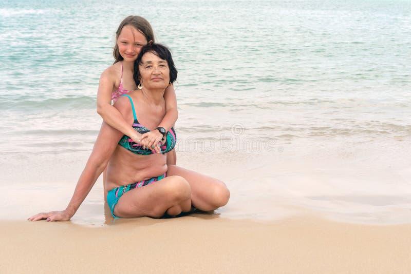 Η γιαγιά αγκαλιάζει την εγγονή μια ηλιόλουστη ημέρα Ευτυχές ανώτερο χαμόγελο γυναικών Έννοια του ηλιόλουστου και ευτυχούς καλοκαι στοκ εικόνες