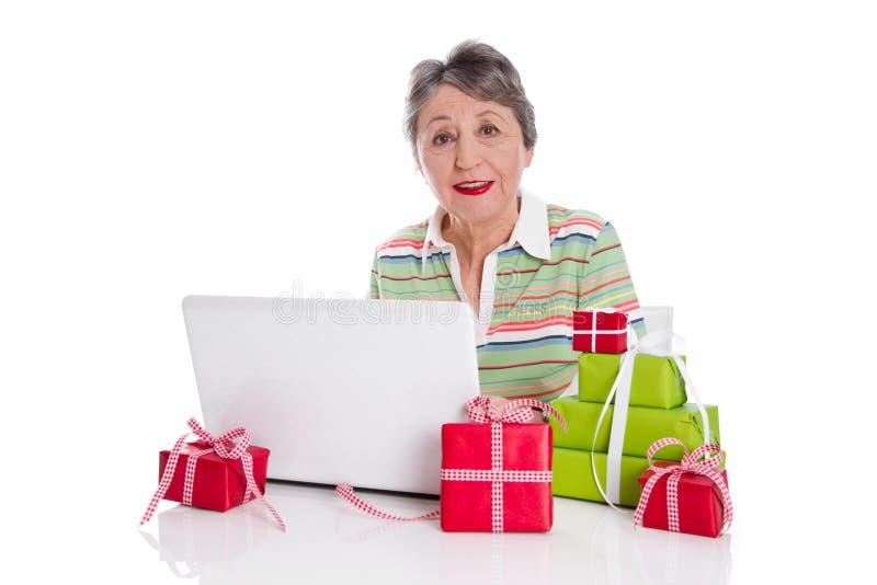 Η γιαγιά διέταξε τα σε απευθείας σύνδεση δώρα - ηλικιωμένη γυναίκα που απομονώθηκε στο λευκό στοκ φωτογραφία με δικαίωμα ελεύθερης χρήσης