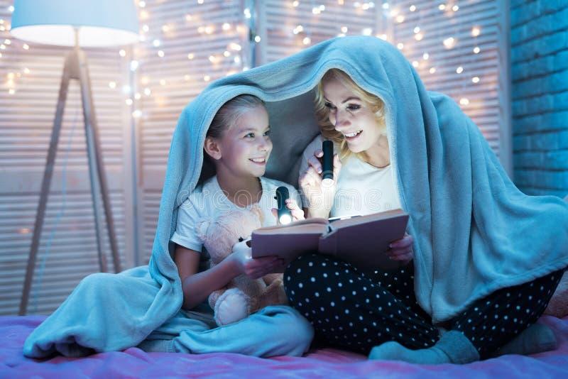 Η γιαγιά και η εγγονή διαβάζουν τα παραμύθια κάτω από το κάλυμμα τη νύχτα στο σπίτι στοκ φωτογραφία με δικαίωμα ελεύθερης χρήσης