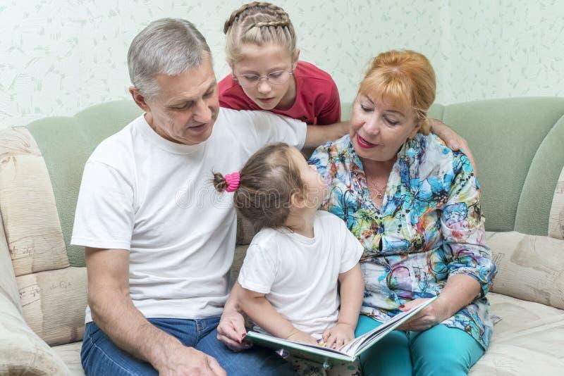 Η γιαγιά και ο παππούς διδάσκουν τις εγγονές στοκ φωτογραφία