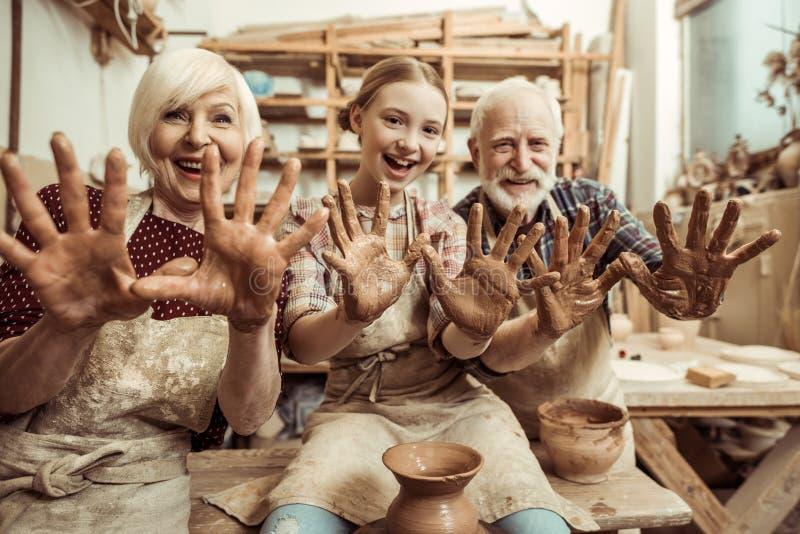 Η γιαγιά και ο παππούς με την παρουσίαση εγγονών παραδίδουν τον άργιλο στοκ εικόνα με δικαίωμα ελεύθερης χρήσης