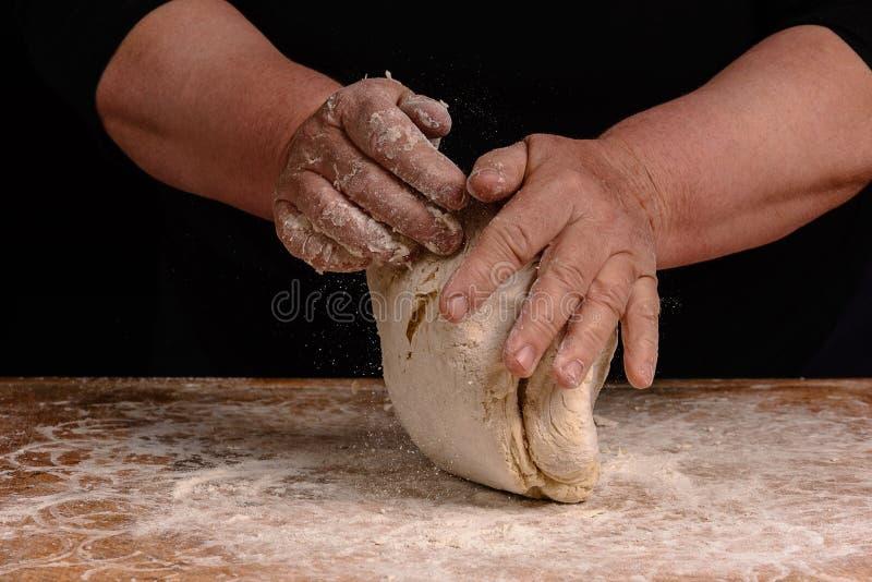 Η γιαγιά μιας ηλικιωμένης γυναίκας ζυμώνει μια ζύμη για το μαγείρεμα του ψωμιού στοκ εικόνες