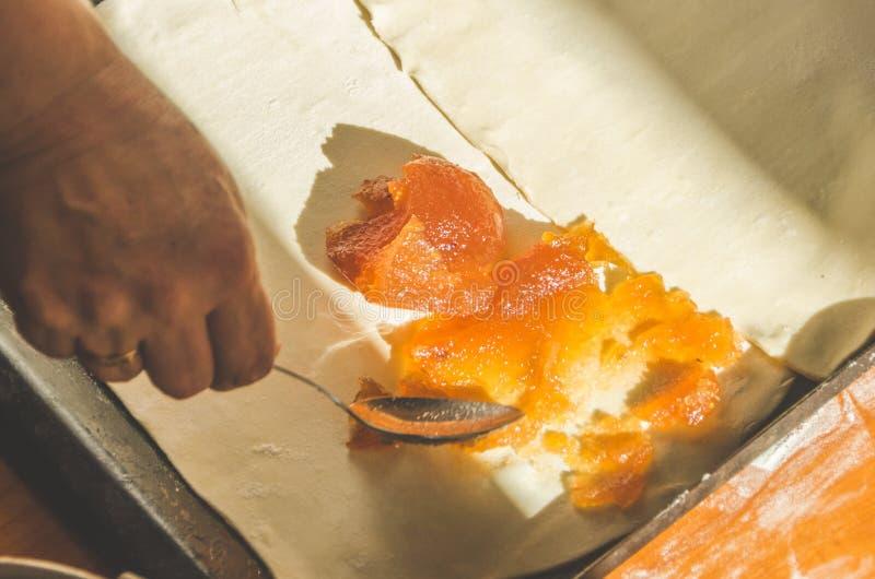 Η γιαγιά προετοιμάζει τις πίτες με τη μαρμελάδα της Apple στοκ εικόνες
