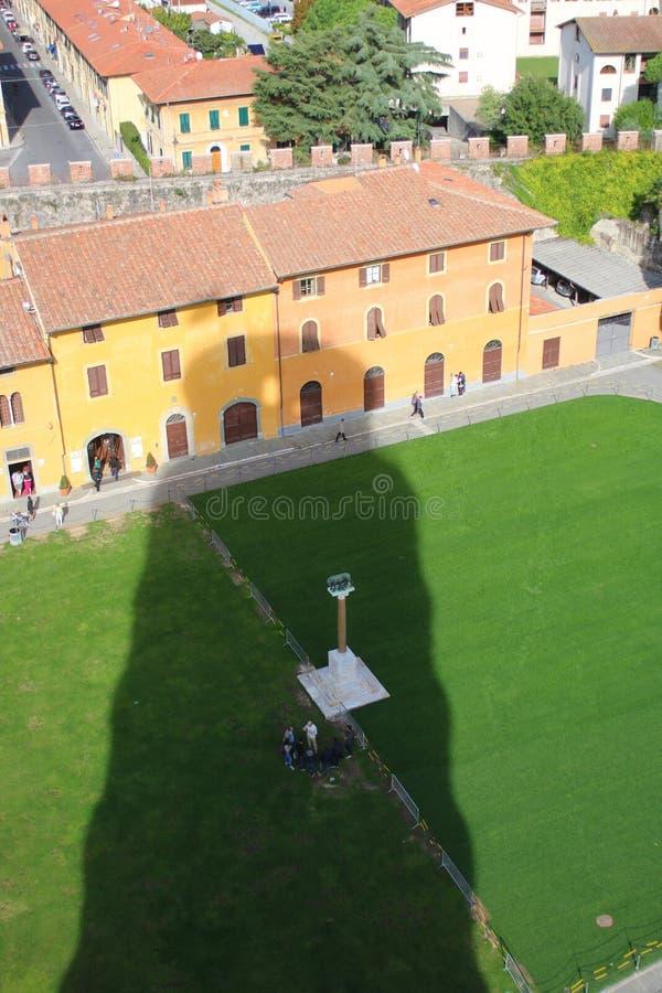 Η γιγαντιαία σκιά του πύργου των αργαλειών της Πίζας πέρα από τα σπίτια και τις οδούς στοκ εικόνα
