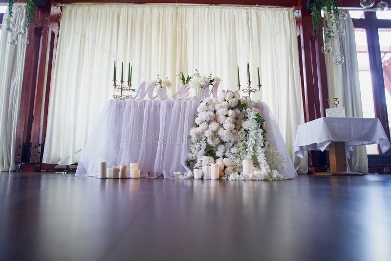 Η γιρλάντα λουλουδιών των πεύκο-διαμορφωμένων τριαντάφυλλων κρεμά από τον πίνακα Γαμήλια διακόσμηση, floristry Κηροπήγια με τα πρ στοκ φωτογραφία
