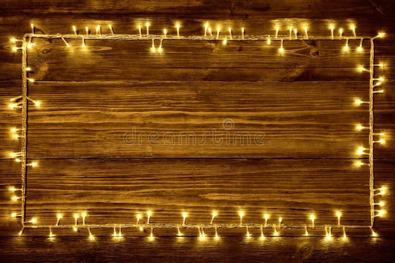Η γιρλάντα ανάβει το ξύλινο υπόβαθρο, ξύλινες σανίδες πλαισίων διακοπών στοκ εικόνες
