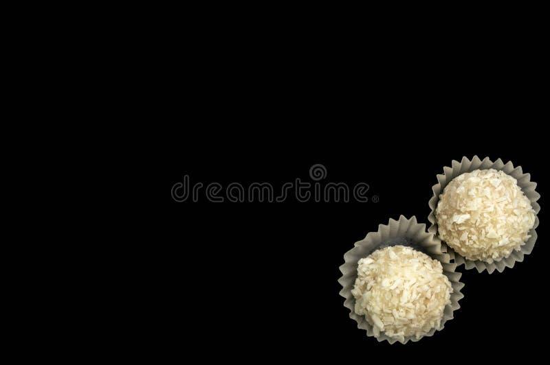 Η γλυκιά άσπρη κρέμα καραμελών με την καρύδα απομονώνει σε ένα μαύρο υπόβαθρο στοκ εικόνες