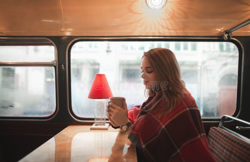 Η γλυκιά κυρία κάθεται σε έναν άνετο καφέ στο παράθυρο που καλύπτεται με ένα κάλυμμα, κρατά ένα φλιτζάνι του καφέ στα χέρια της κ στοκ εικόνα με δικαίωμα ελεύθερης χρήσης